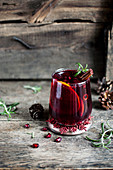 Cherry and pomegranate mocktail with orange, cinnamon and rosemary