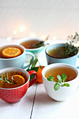 Cups of tea with various herbs and orange slices