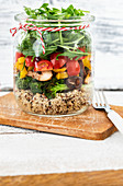 Salad in a jar with quinoa, mushrooms, broccoli, pepper, tomatoes and rocket
