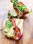 A roll topped with avocado, bacon, cheese and pea sprouts