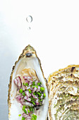 An open oyster with chives and onions