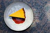 Ein Stück Mangotarte mit Joghurtcreme, Keksboden und Beerensauce