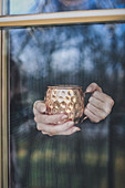 Hands behind a window holding a copper mug