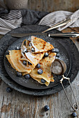 Crepes with blueberries, honey and icing sugar for breakfast