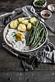 Simple vegetarian lunch with fried egg, cooked potatoes and green beans with butter and breadcrumbs