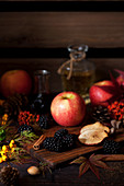 Apples and blackberries on a wooden board with autumn foliage