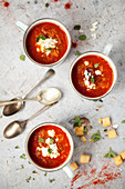 Enamel cups with smoky tomato soup topped with feta and herbs