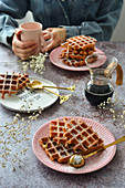 Waffles on a saucer on the table a jug of coffee a mug The woman is holding a cup in her hands