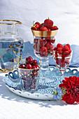 Gläser mit Süßkirschen, Erdbeeren und Himbeeren auf Tablett