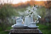 Weißes Kaffeegeschirr und Gießkanne mit Apfelblütenzweigen auf Steinplatte im Freien