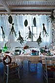 Festlich dekorierter Esstisch mit Lichterkette und aufgehängten Sträussen aus Zweigen