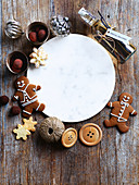 Christmas biscuits, sweets and decorations around a marble plate