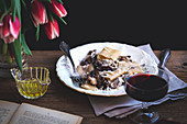 Pasta with radicchio, panceta and Parmesan served on a plate, on a rustic wooden table