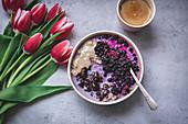 Ein Schälchen Porridge mit Schokolade, Tahini und Blaubeeren zum Frühstück