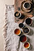 Stillleben mit verschiedenen Teesorten, aufgebrüht und als Teeblätter