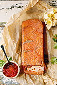 Red salmon caviar in ceramic bowl and homemade salmon terrine served with butter