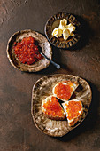 Red salmon caviar in bowl and on wheat bread, served with butter