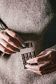 Woman beige sweater hold in hands broken dark chocolate bar