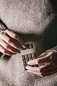 Frau hält Schokoladentafel und abgebrochenen Riegel in den Händen