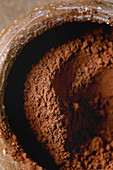 Cocoa powder in ceramic bowl with cocoa beans over brown texture background. Flat lay, close up