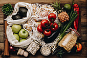 Zero waste food shopping. Fruit and vegetables in cotton bags, pasta, cereals and legumes in glass jars, herbs and spices on wooden background