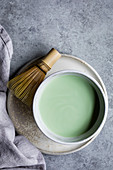 Matcha tea in a bowl with a matcha whisk next to it