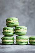 Matcha-Macarons mit Mangobuttercreme vor grauem Hintergrund