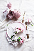 Posies of pink carnations tied with ribbons on plates