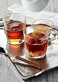 Earl Grey Tee mit Milch in Teegläsern auf silbernem Tablett