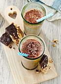 Hot chocolate in glasses with homemade muesli bars with chocolate glaze