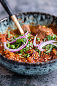 A bowl of beef curry with red onions and coriander