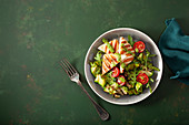 Courgette salad with grilled halloumi, tomatoes and pesto