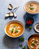 Carrot soup with coconut milk, red chillies, cilantro, white and blach sesame seeds