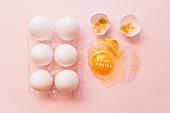 Osterstilleben mit aufgeschlagenem Ei, Eierschalen und Goldglitter