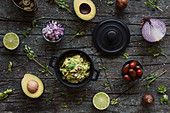 Various fresh ingredients placed on lumber table near pot with yummy guacamole