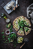 Pizza with greenery slices of squash on table with spices olive oil cheese for vegetarian dinner