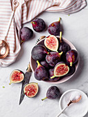 A bowl of ripe, purple figs on a white marble countertop surrounded by a striped napkin, rose gold spoons, and a small bowl of sugar