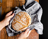 Hands placing a freshly baked loaf of bread wrapped in a grey cloth onto a wood tabletop.