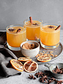 Three glasses of an orange spiced drink, garnished with cinnamon sticks, brown sugar, blood oranges, and star anise