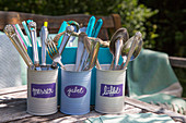 Handmade cutlery holders made from tin cans painted in pastel shades