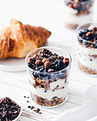 Granola in a glass with yoghurt, berries and cocoa nibs