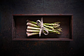 A bundle of fresh green asparagus in a wooden box on a dark surface