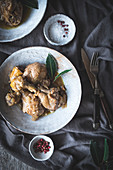 Stewed chicken drumsticks with broth in white ceramic bowl