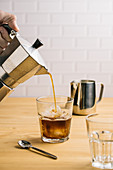 Pouring coffee from coffeemaker into stylish glass with ice on wooden counter in cafe