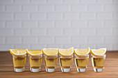 Tequila-Shots mit Zitrone in einer Reihe