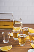 Glass shots of golden tequila with salty rim and slices of lemon on top