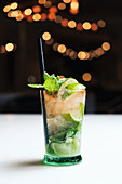 Glass cup of cold mojito with straw placed on counter against blurred background in pub