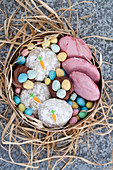 Easter cookies with pink and carrot decorations, chocolate cupcakes and mini chocolate eggs