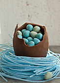 Large chocolate Easter egg, sitting in a blueberry candy nest, filled with mini chocolate eggs