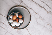 Mixed colour eggs in bowl on marble surface